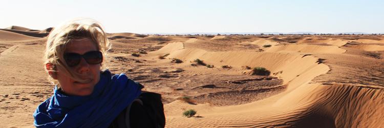 Petra met zonnebril op en fleecejas aan in de woestijn