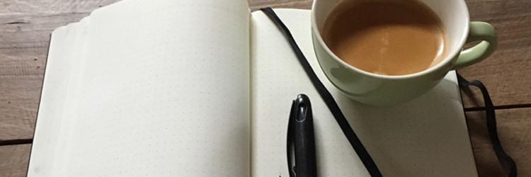 leeg notitieboek met pen en kop koffie