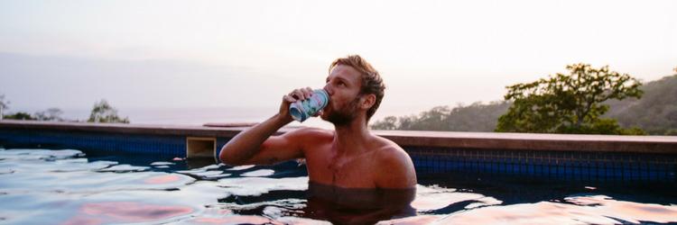 man zit in zwembad en drinkt blikje bier