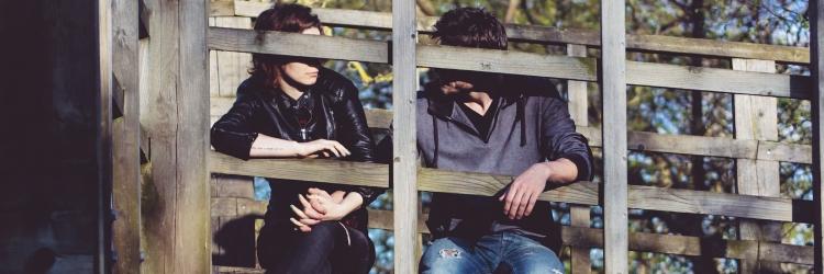 man en vrouw pratend op een houten brug