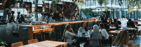 4 vrouwen drinken koffie en praten in modern cafe